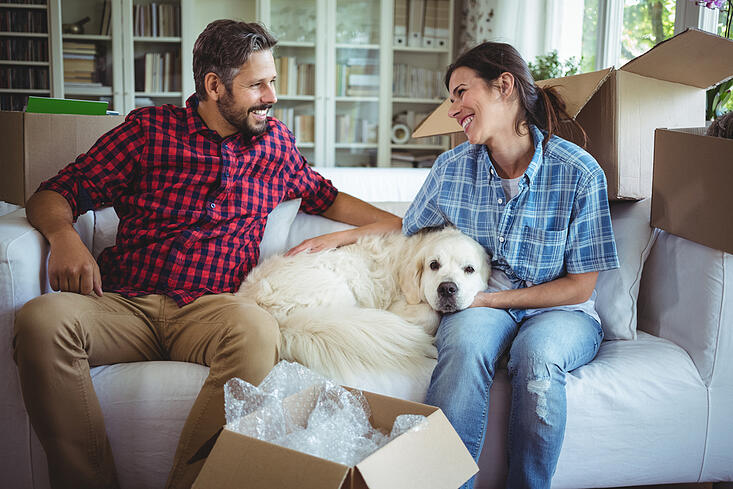 Couple sitting on sofa with their pet dog in their new house