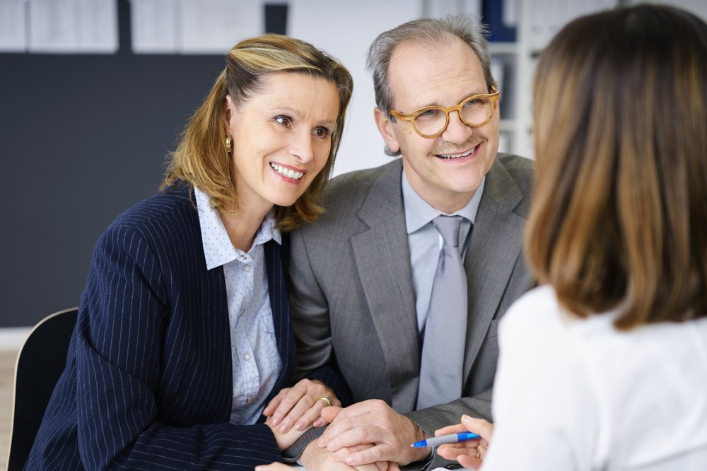 Smiling middle-aged couple in a meeting with an investment adviser planning for their future retirement, over the shoulder view