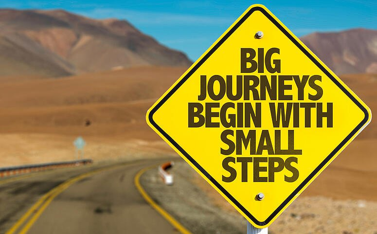 Big Journeys Begin With Small Steps sign on desert road