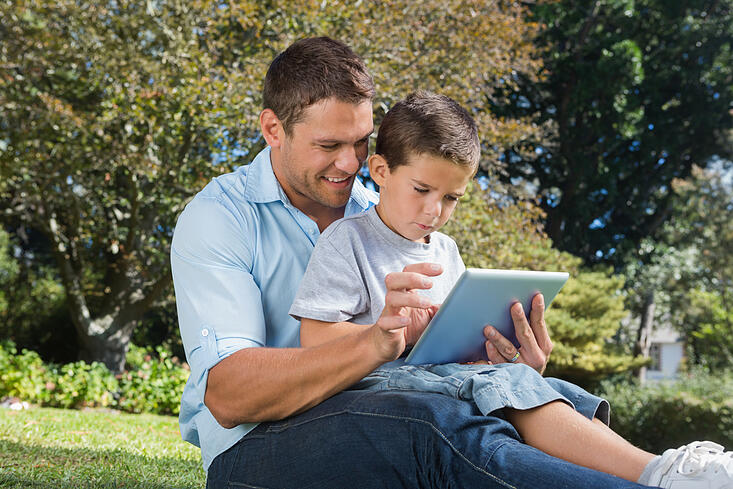 Dad and son using a tablet pc in a park on sunny day