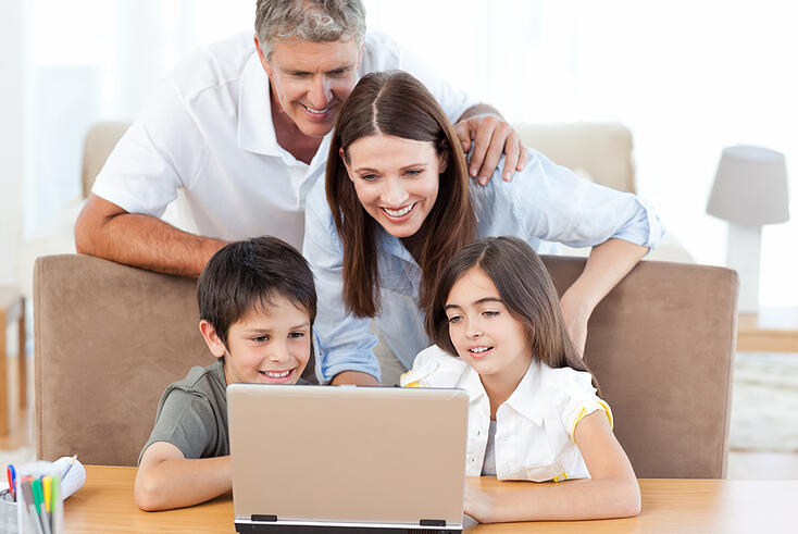 Family looking at the laptop at home