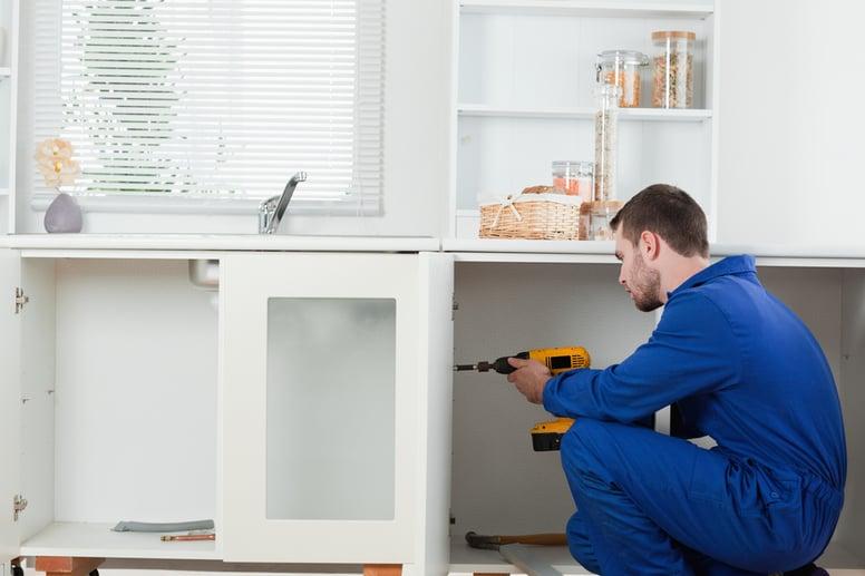 Good looking handyman fixing a door in a kitchen-3