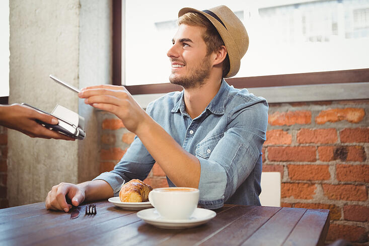 Handsome hipster paying with smartphone at coffee shop