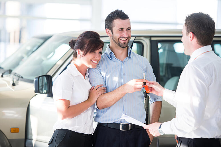 Happy couple getting car keys from a car seller-1