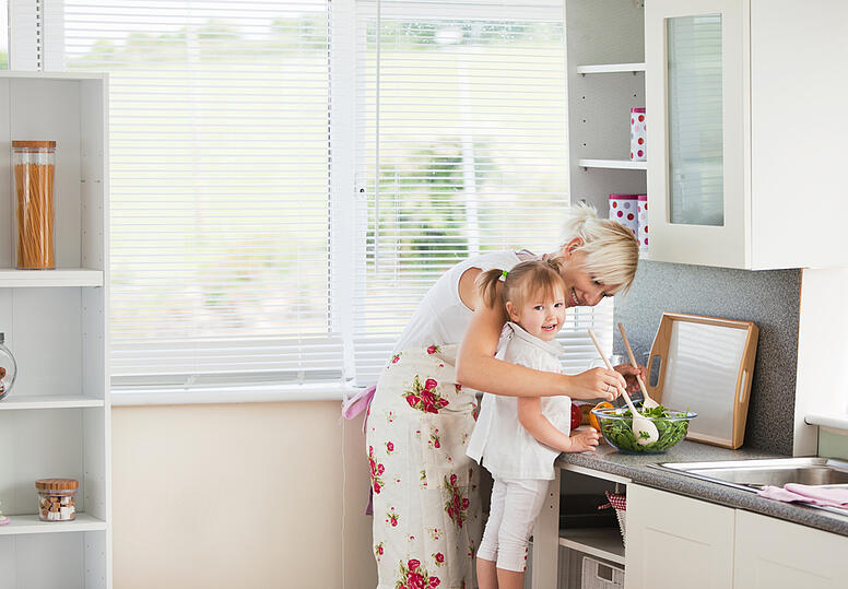 Jolly girl preparing a salad with her mother in the kitchen