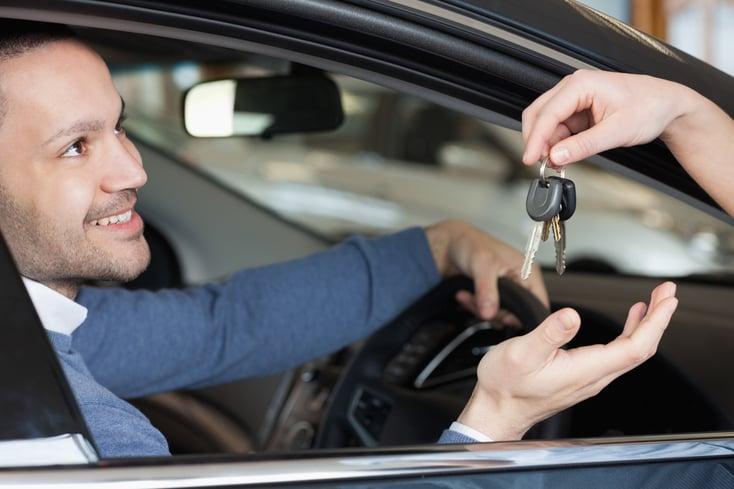 Man receiving keys while sitting in a car