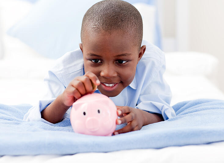 Young Boy lying on his bed putting money into a piggy bank-1