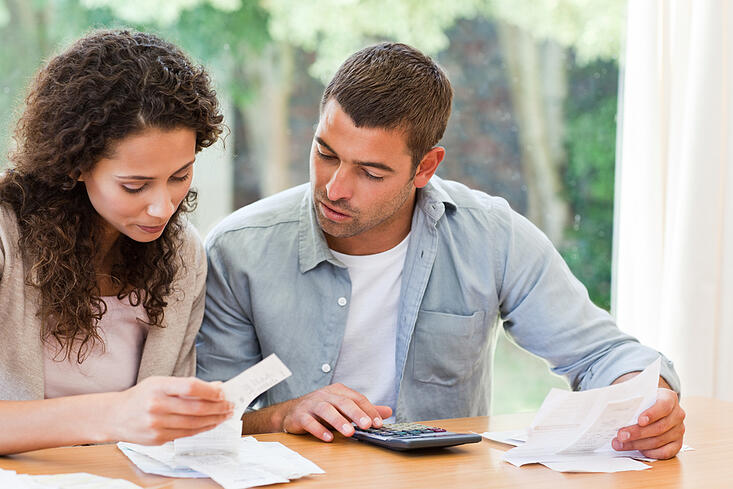 Young couple calculating their domestic bills at home