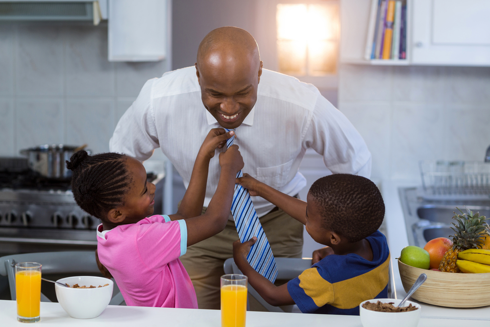 Children helping their father in tying tie at kitchen