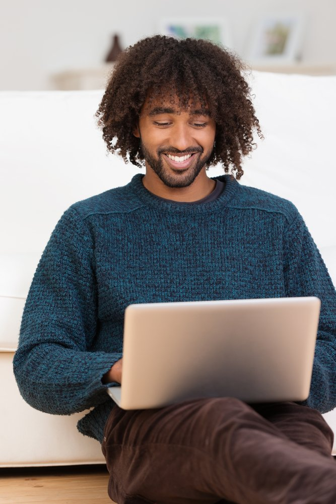 Handsome hip young African American man smiling as he types on his laptop computer while relaxing on the floor in the living room