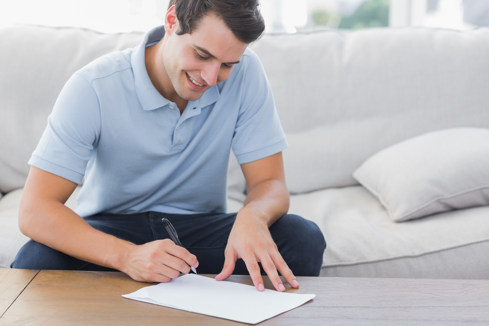 Man writing on a paper while he is sat on a couch