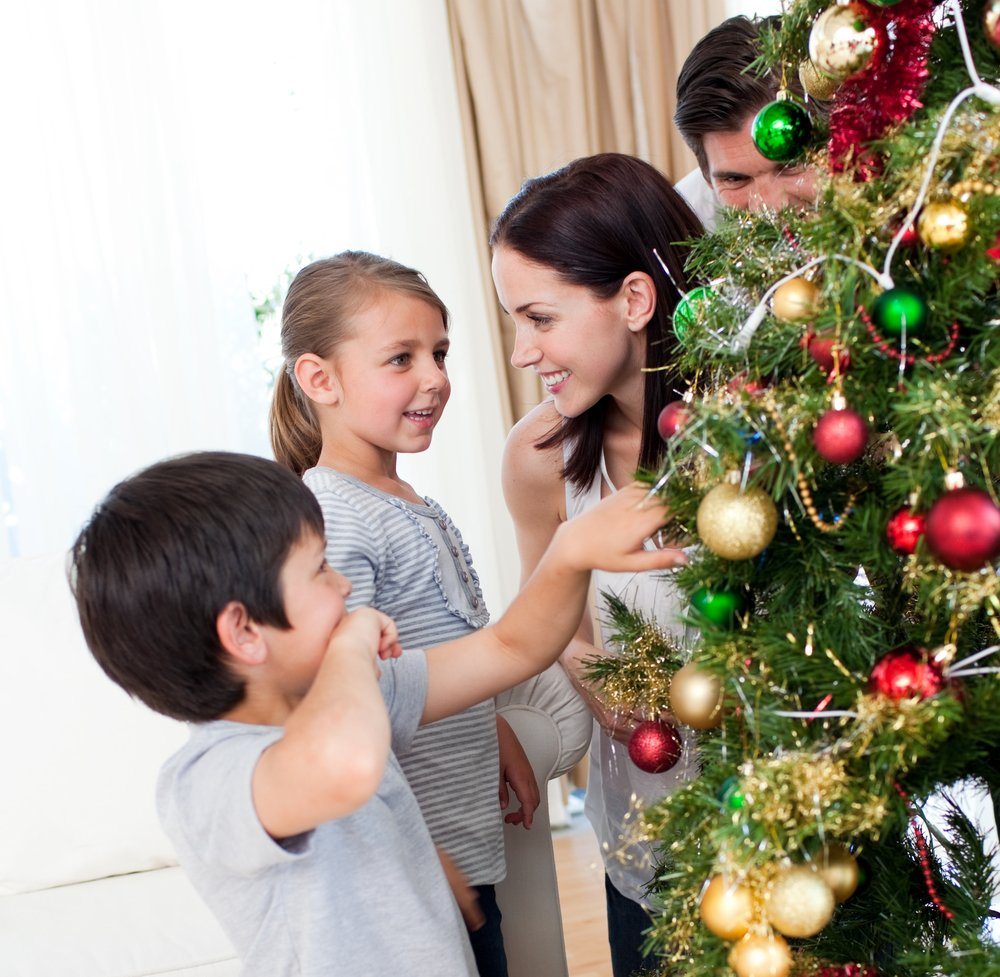 Smiling family decorating a Christmas tree with boubles in the living-room