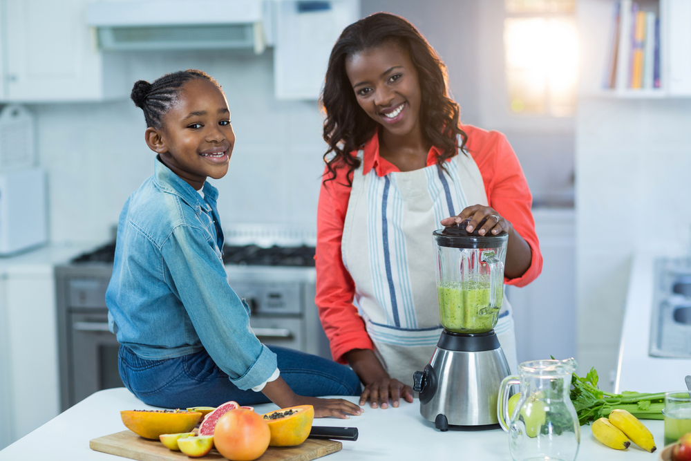 Woman and daughter using mixer in kitchen